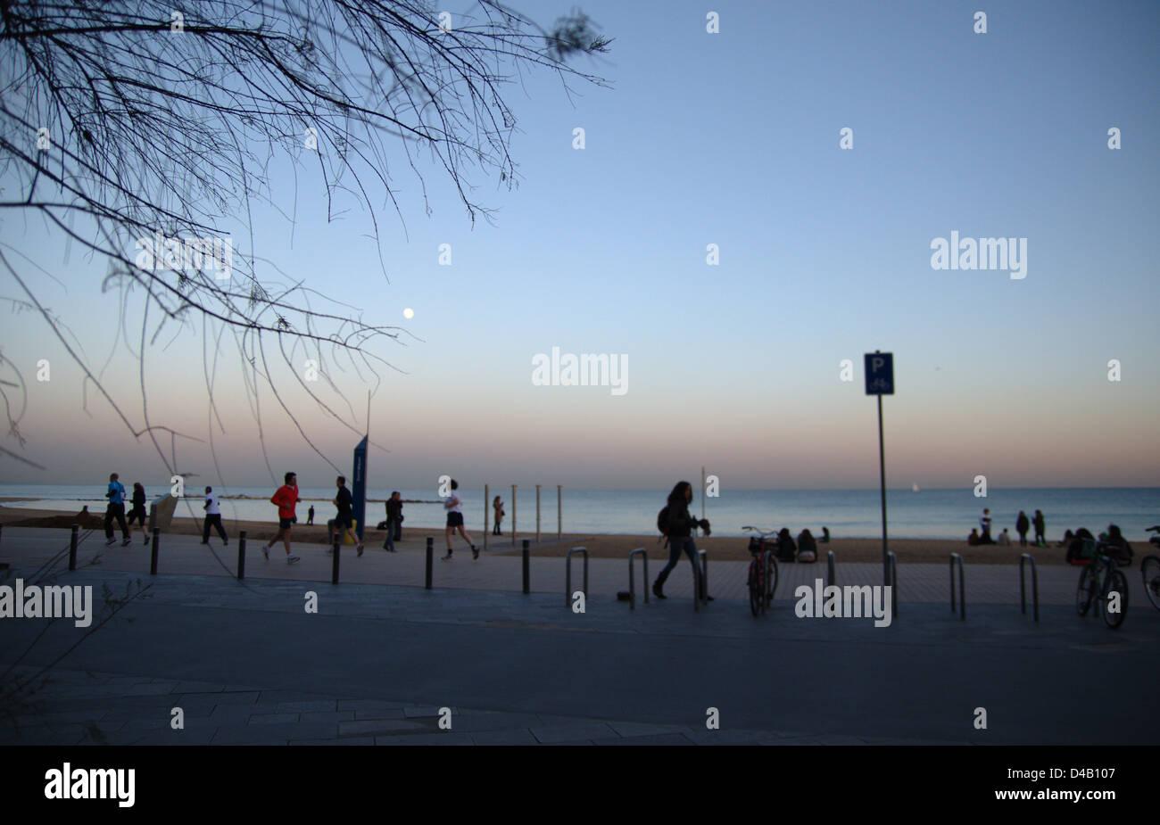 Ambient sulla spiaggia di Barcellona di notte. Le persone che eseguono presso il lungomare. Immagini Stock