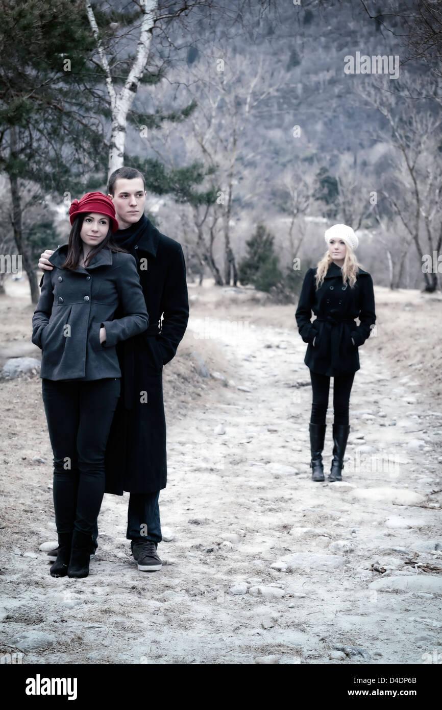 Un giovane sotto braccio e una seconda donna è lasciato alle spalle Immagini Stock