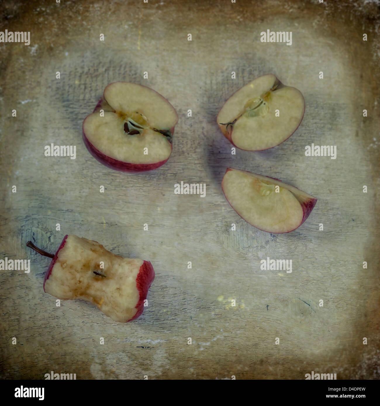 Un apple, tagliato in tre pezzi e un mezzo mangiato apple Immagini Stock
