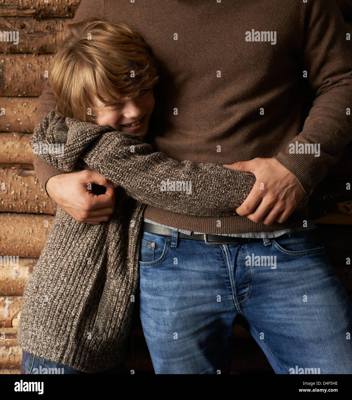 Sorridente figlio abbraccia il padre Foto Stock