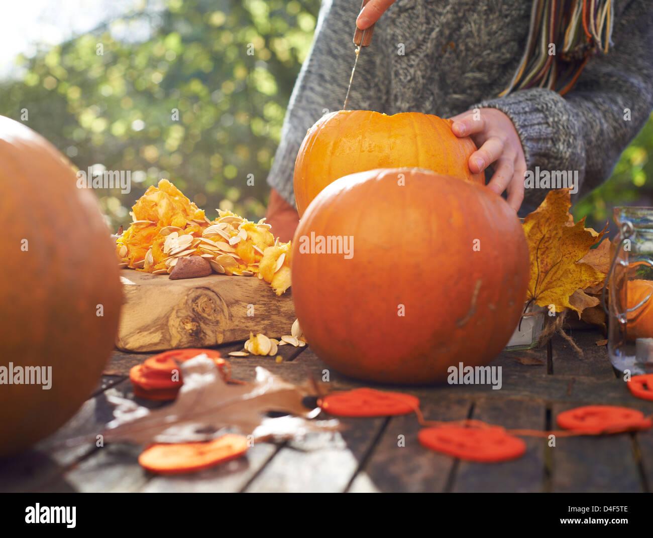 Ragazzo adolescente carving zucche all'aperto Immagini Stock