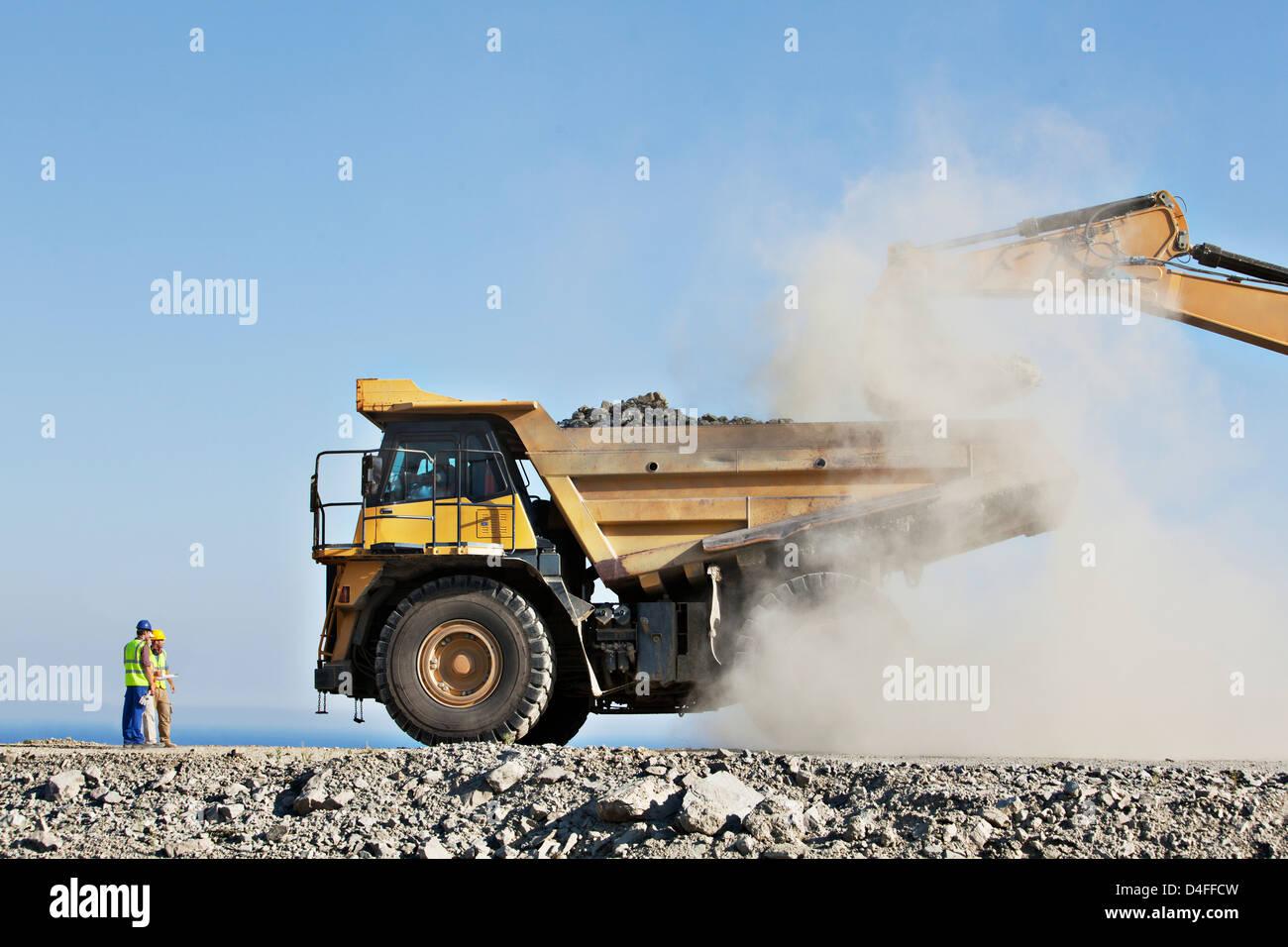 I lavoratori di supervisionare digger e carrello in cava Immagini Stock