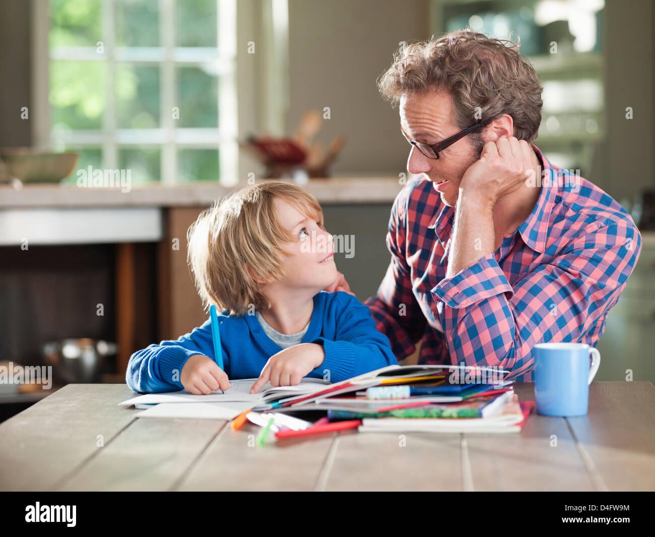 Padre e figlio di fare i compiti al tavolo della cucina Immagini Stock