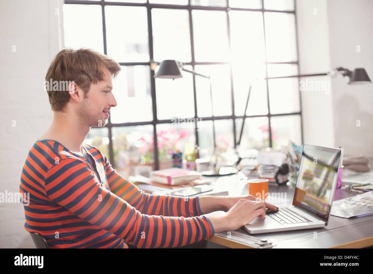 Uomo con notebook alla scrivania Immagini Stock