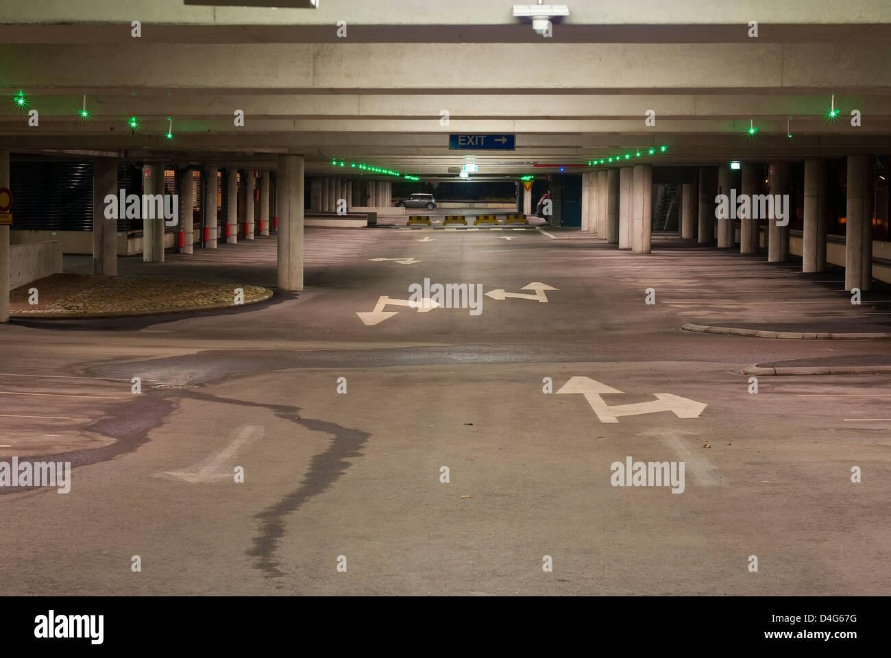 Vuoto parcheggio garage con poca luce verde per illuminare i posti