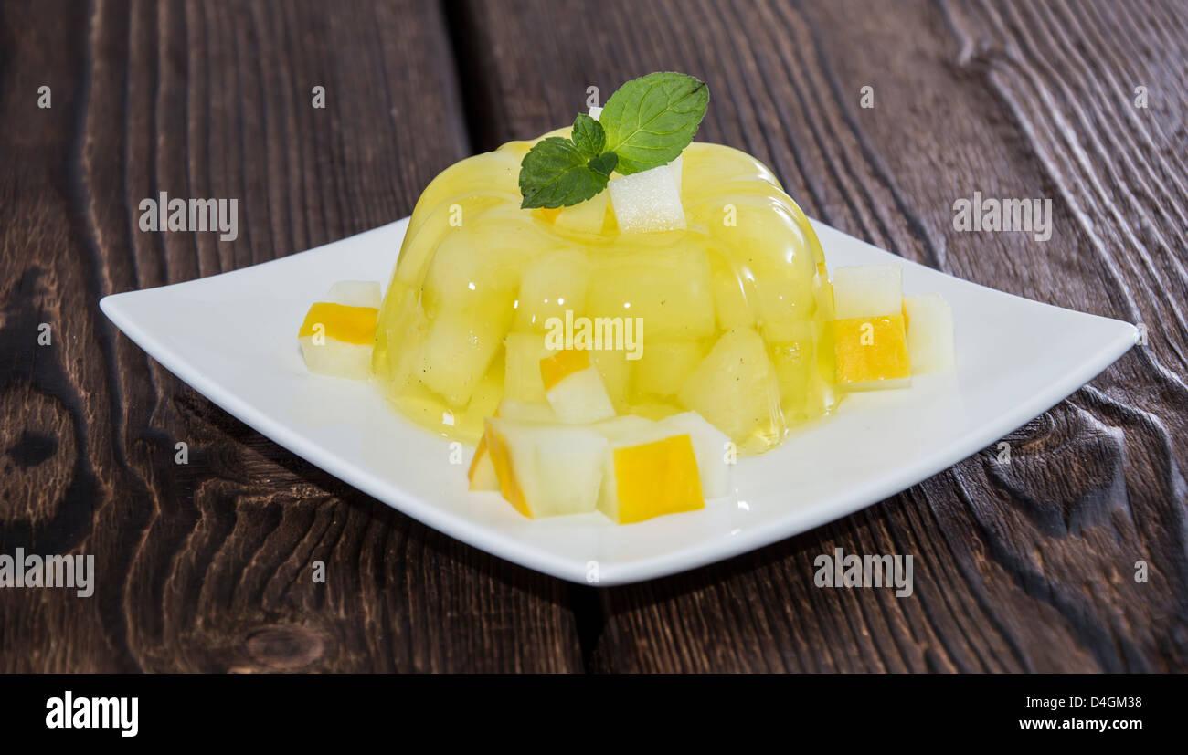 In casa di melata jella con pezzi di frutta su sfondo di legno Immagini Stock