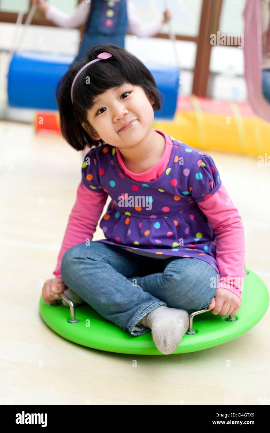 Carino ragazza seduta su un grande dreidel giocattolo in kindergarten Immagini Stock