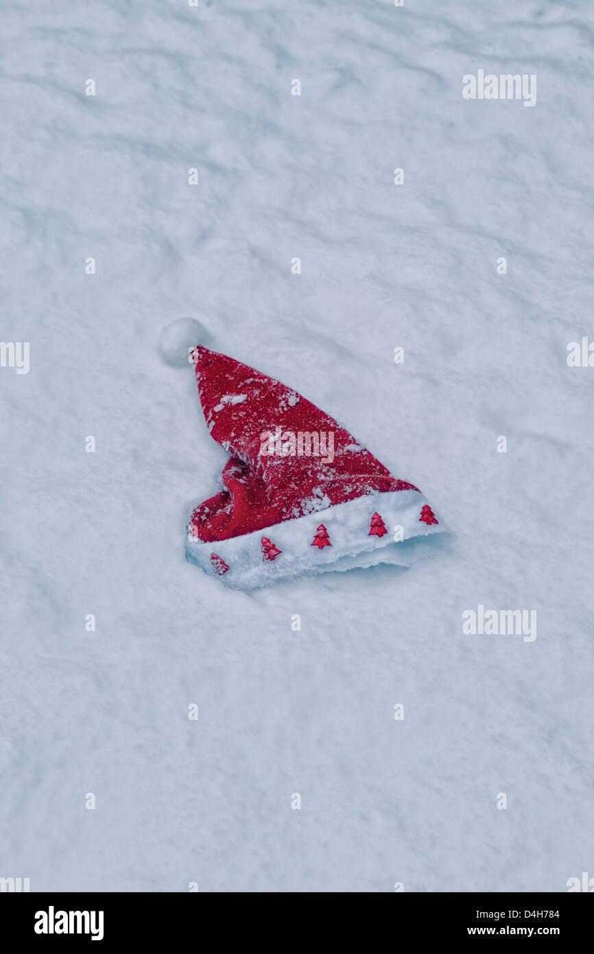 Un cappello da Babbo Natale che giace nella neve Immagini Stock