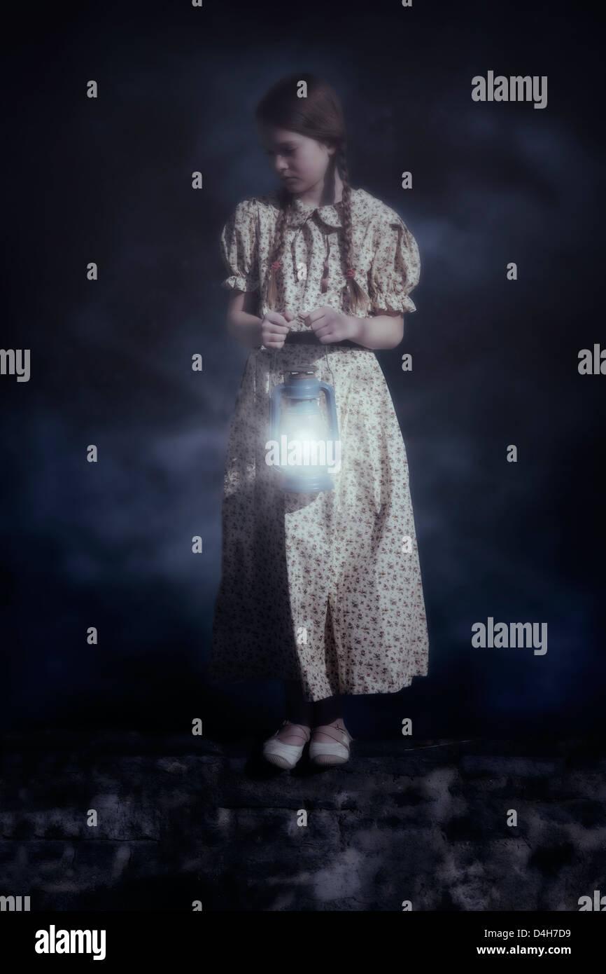 Una ragazza con una lanterna in piedi su una parete Immagini Stock