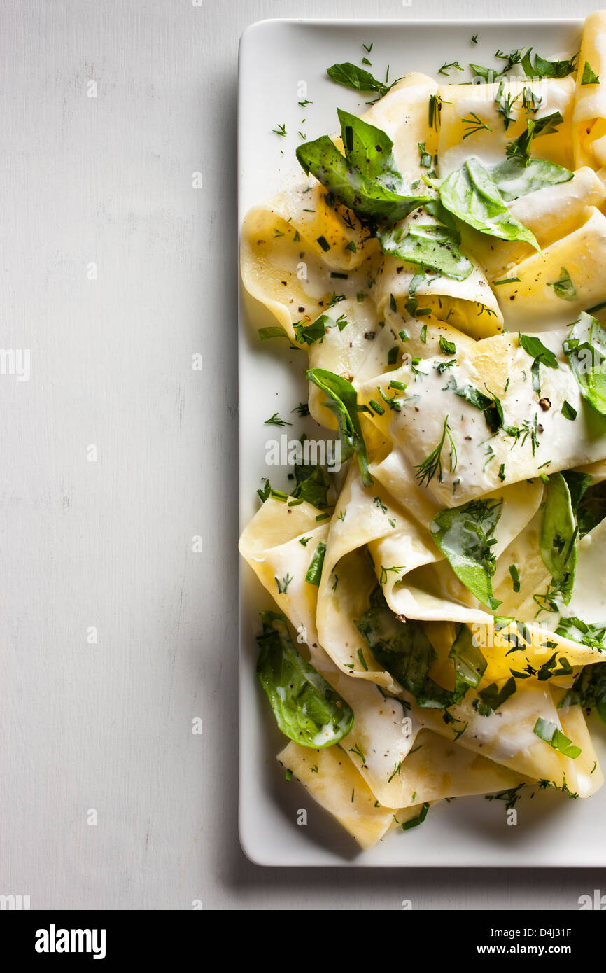 Un piatto di pappardelle con crema di ricotta, baby spinaci erbe fresche e pepe nero. Immagini Stock