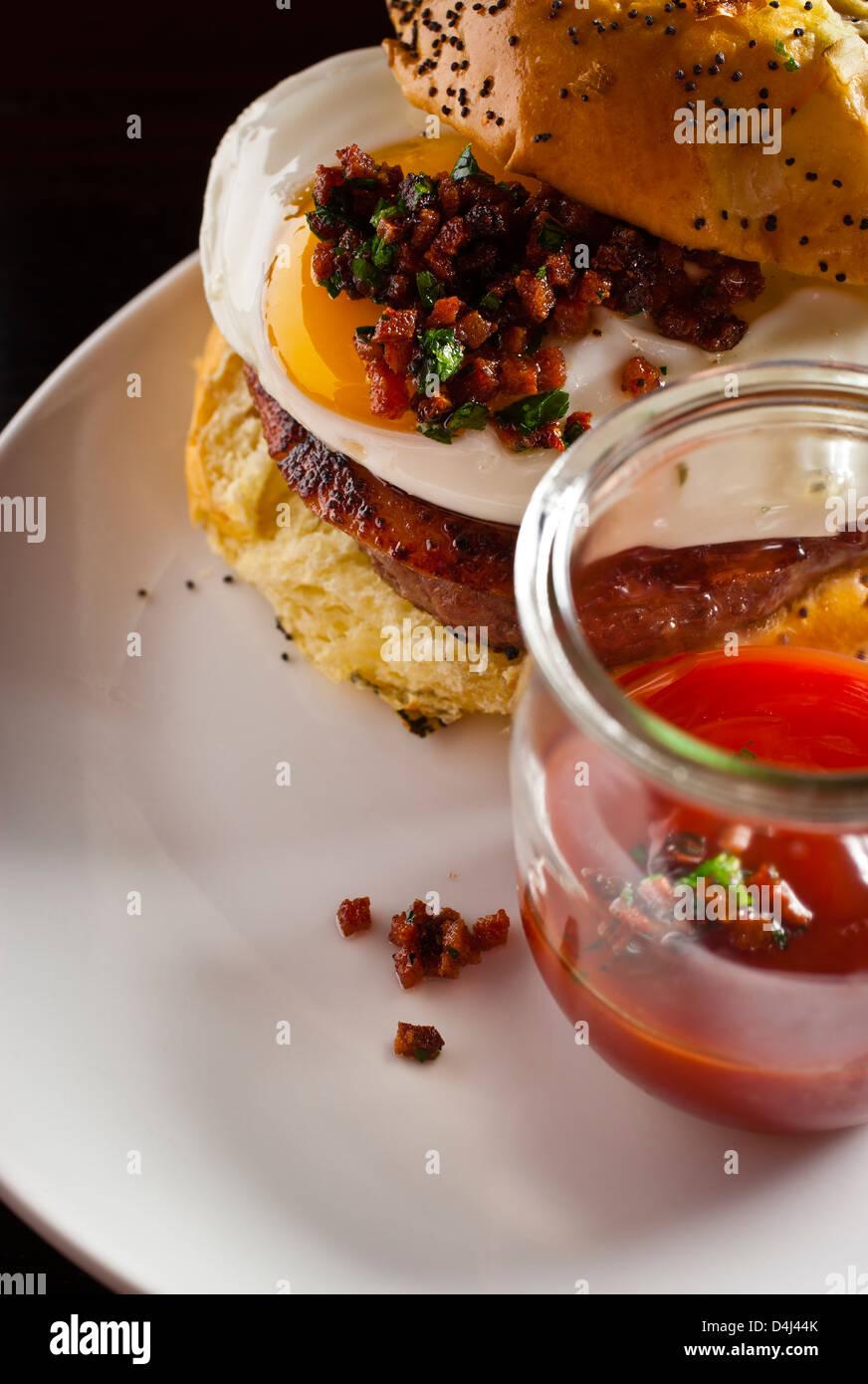 Burger Royal, con sunny side up di uova, prosciutto e ketchup preparato da Rob Ruban, Executive Chef del traversino Immagini Stock