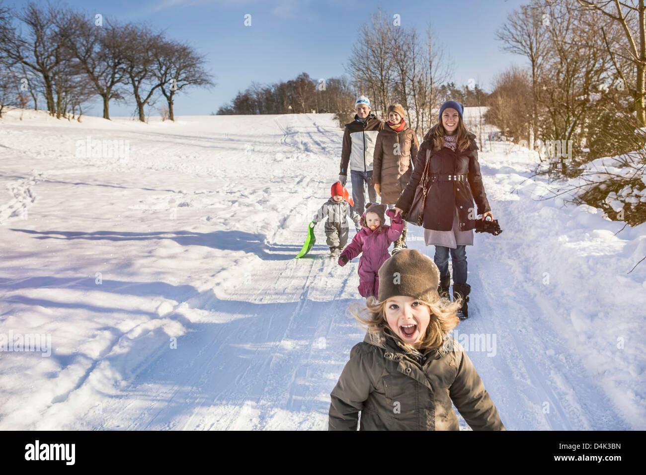Famiglia camminare insieme nella neve Immagini Stock