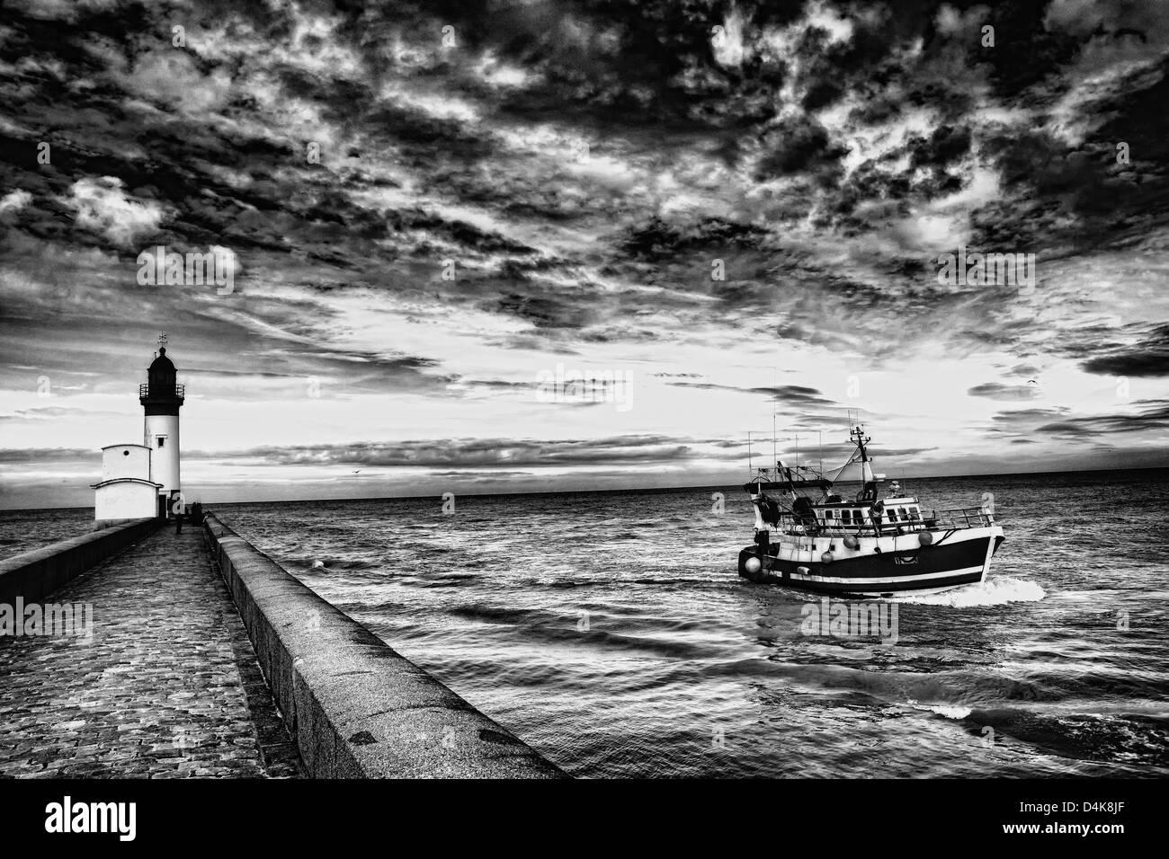 Nave a vela di pietra dal molo sulla spiaggia Immagini Stock