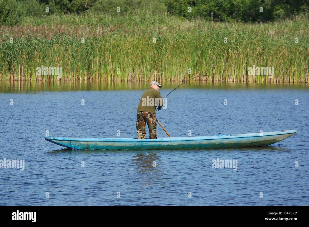 Un pescatore cale verso l'interno un pesce su un Lago Mueritz National Park vicino a Rechlin, Germania, 14 agosto Immagini Stock