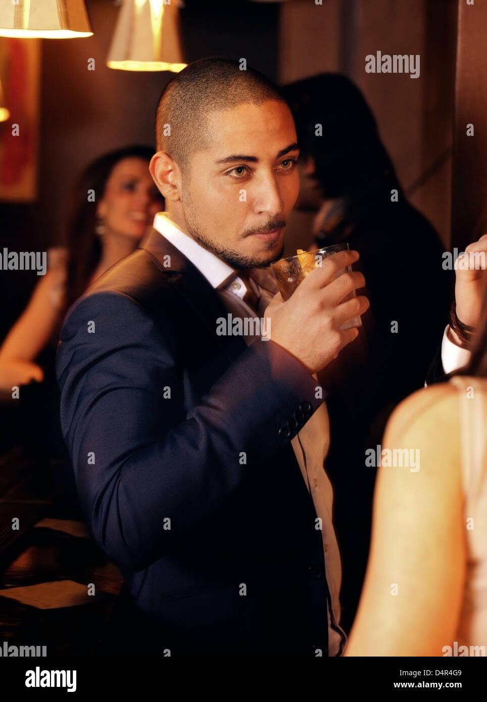 Ritratto di un ragazzo a un partito tenendo un bicchiere di Whiskey Immagini Stock