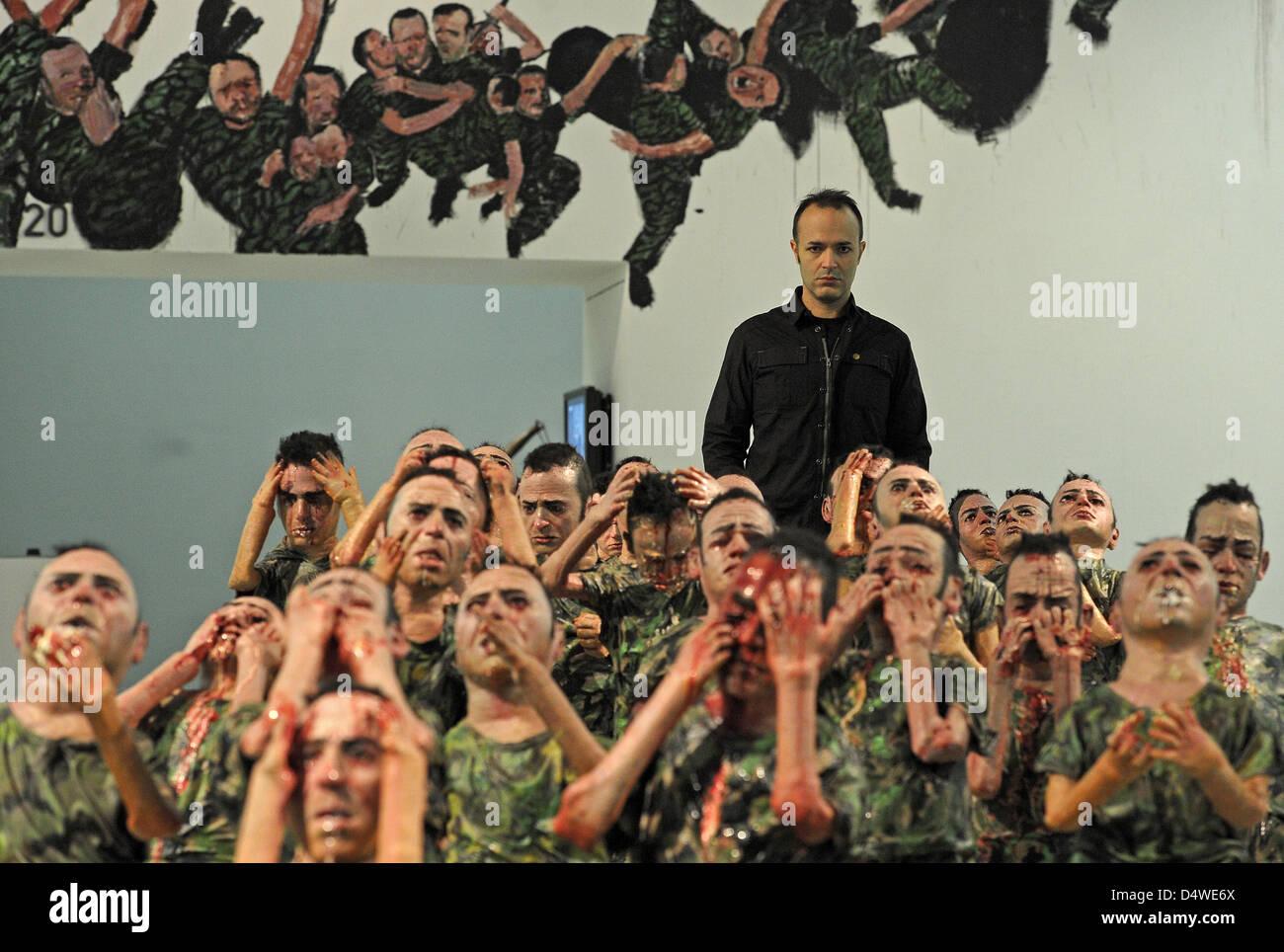 """Artista Enrique Marty è raffigurato con la sua scultura """"fanatici 80', i quali hanno tutti il volto Immagini Stock"""