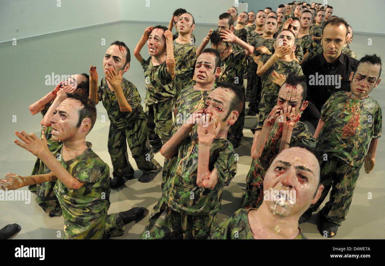 """Artista spagnolo Enrique Marty (C) si inginocchia tra le sue sculture """"fanatici 80', i quali hanno tutti Immagini Stock"""