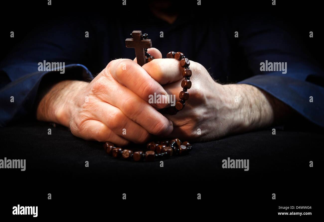 Mani tenendo i grani del rosario e croce pregando. Immagini Stock