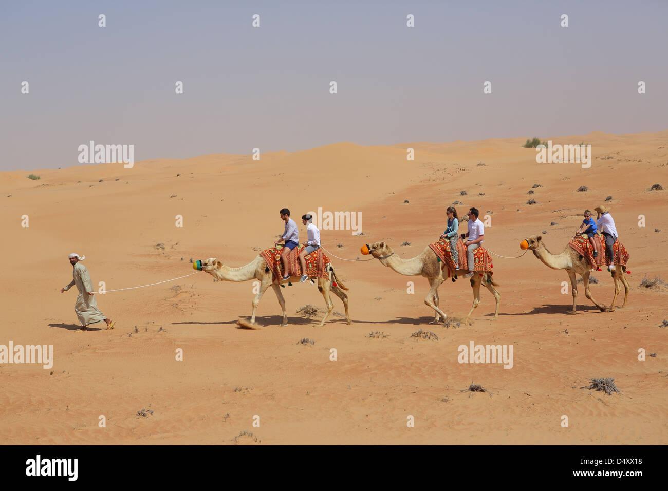 I turisti a cavallo di cammelli nel deserto, Dubai, Emirati Arabi Uniti Immagini Stock