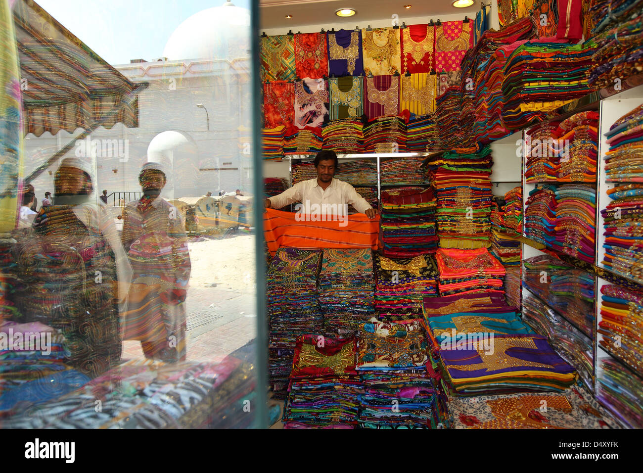 Uomo che piega il tessuto in negozio di tessuti, Dubai, Emirati Arabi Uniti Immagini Stock