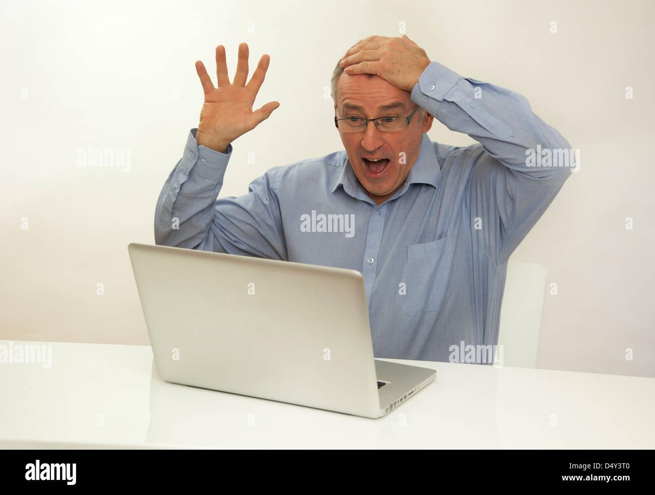 Overjoyed man mano sulla testa guardando uno schermo portatile, felice che ha vinto un premio. Immagini Stock