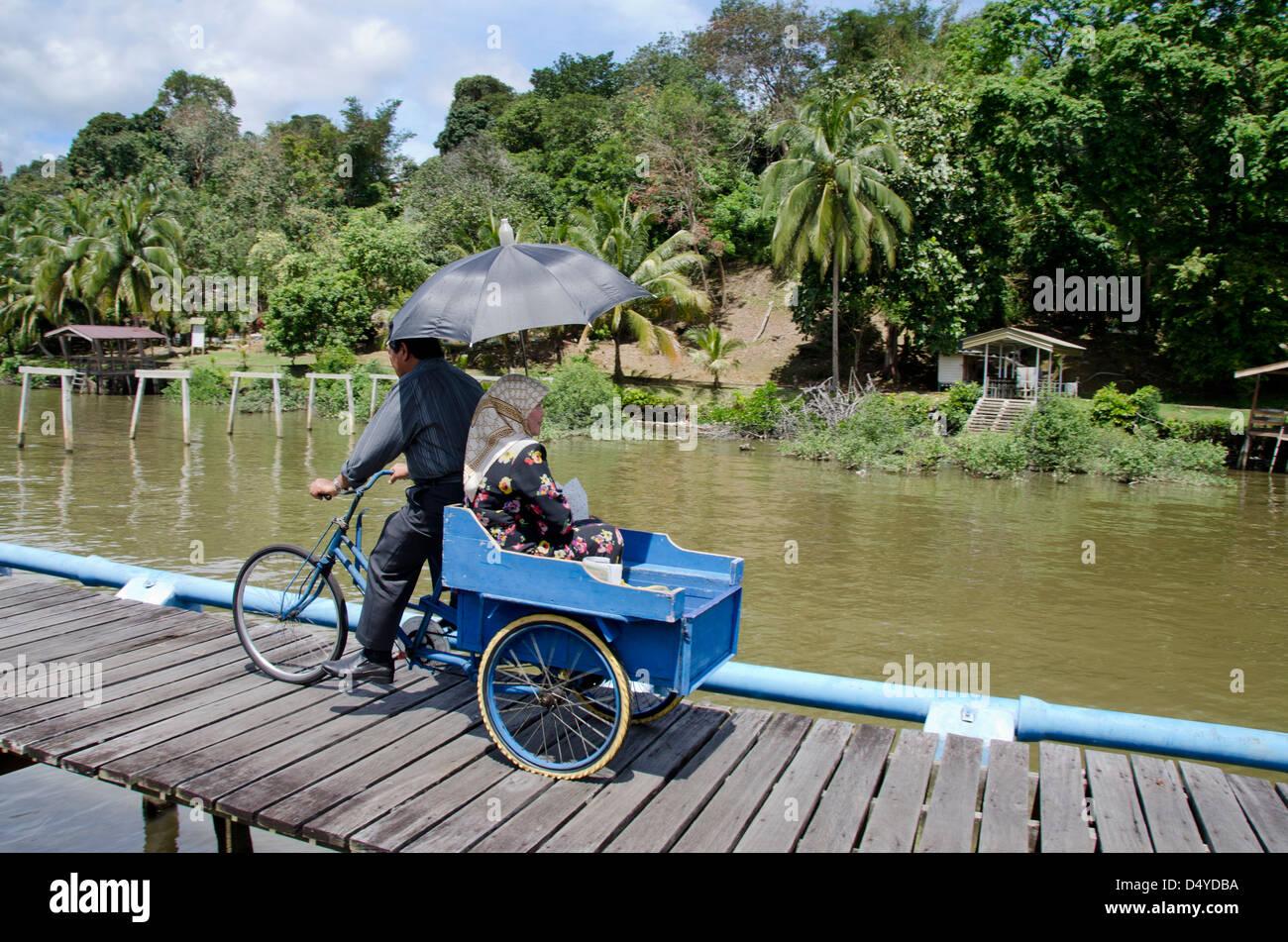 Borneo, Brunei Darussalam. Distretto di Bandar Seri Begawan. Uomo in bicicletta con la donna sul retro. Immagini Stock