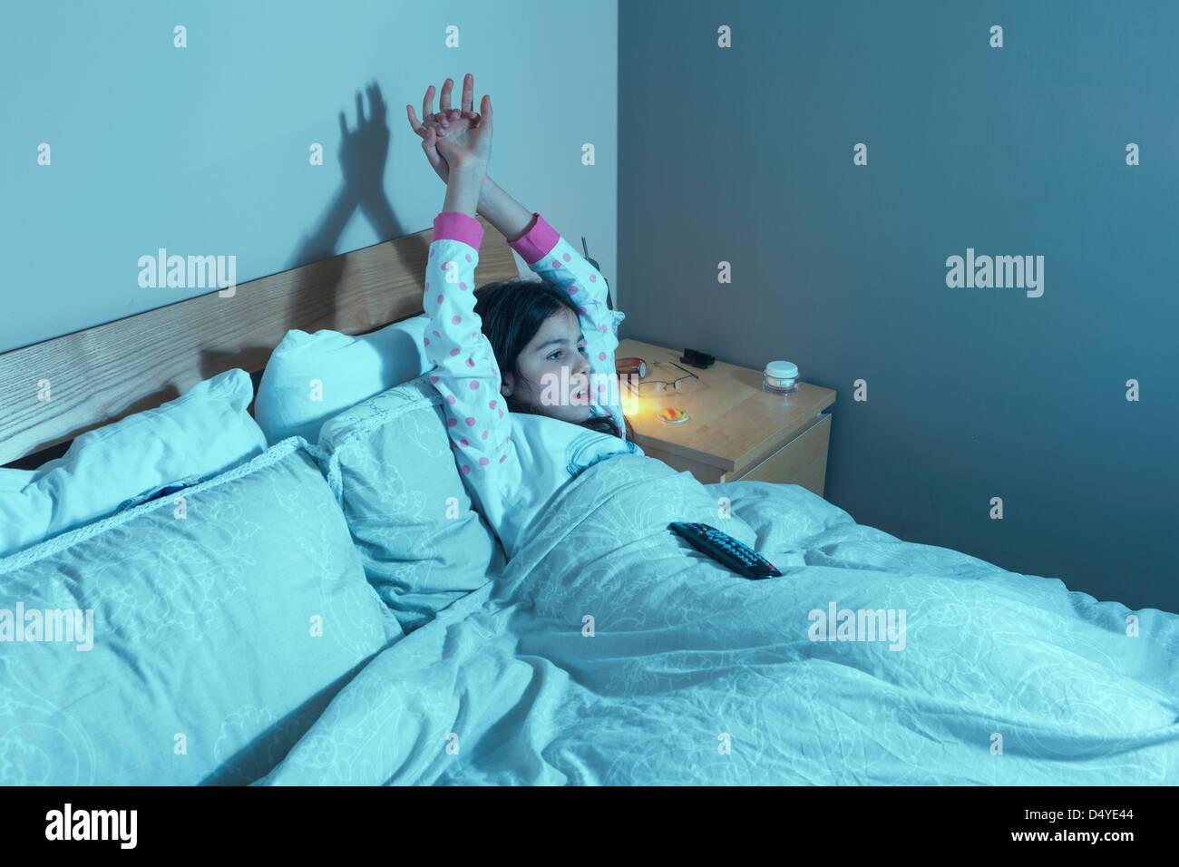 Giovane ragazza guarda la televisione a letto Immagini Stock