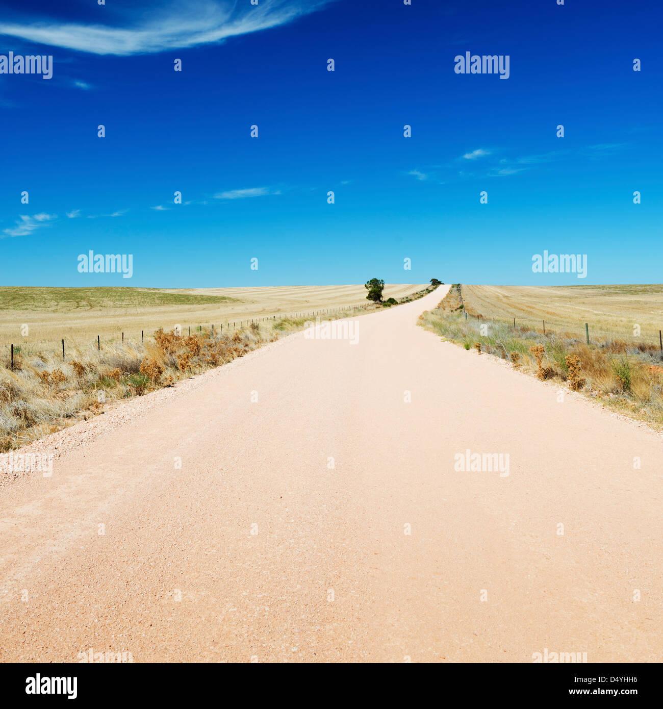 Strada sterrata nel paese Australia si estende nella distanza sotto un cielo blu Immagini Stock