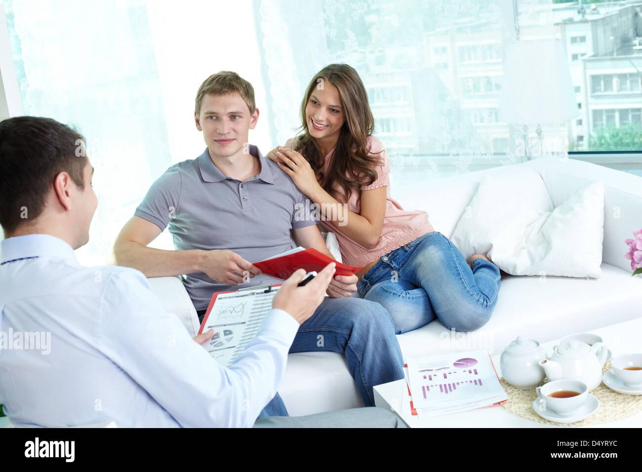 Coppia giovane discute la loro strategia di investimento con un consulente finanziario Immagini Stock