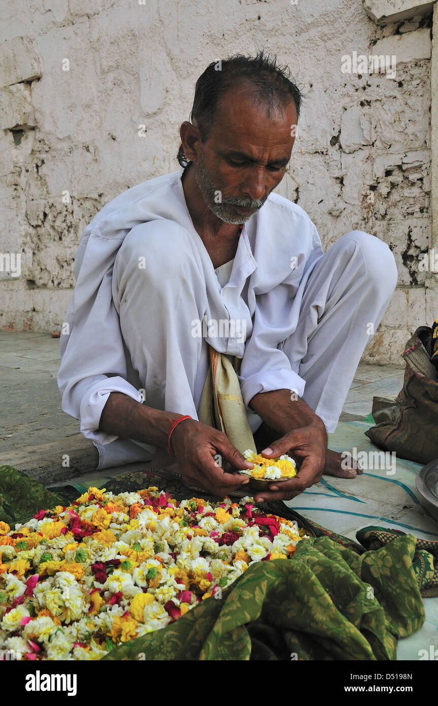 L'uomo che fa ghirlanda di fiori per il culto Immagini Stock