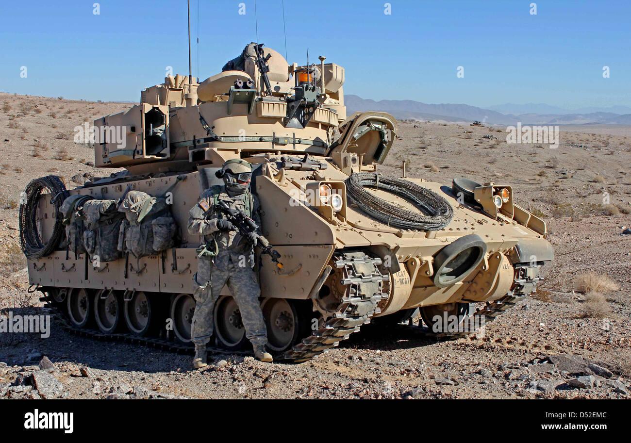 Un US Army soldier prende il coperchio accanto a un M2 Bradley di combattimento della fanteria veicolo durante una Immagini Stock