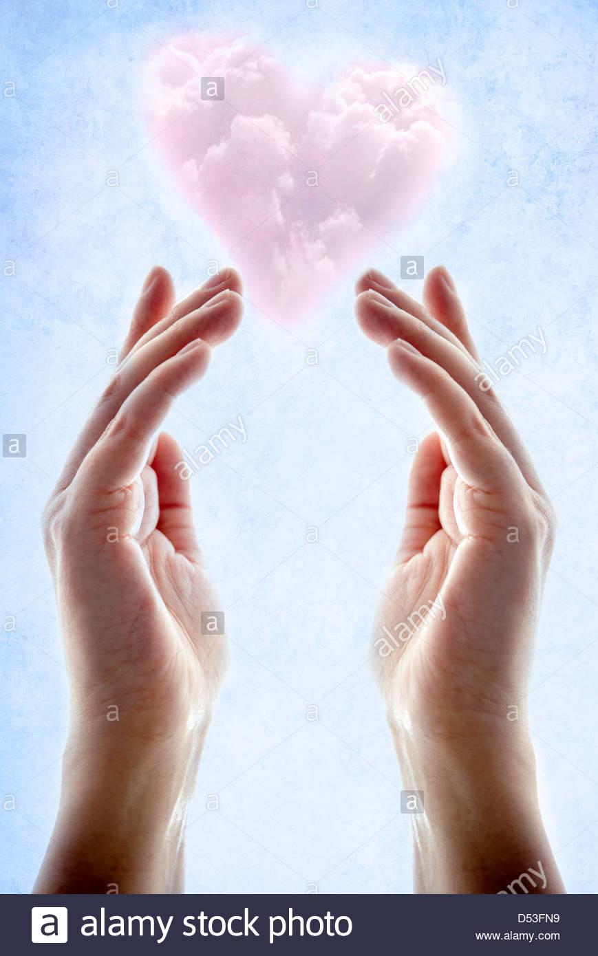 Mani con rosa a forma di cuore il cloud galleggiante sopra di loro Foto Stock