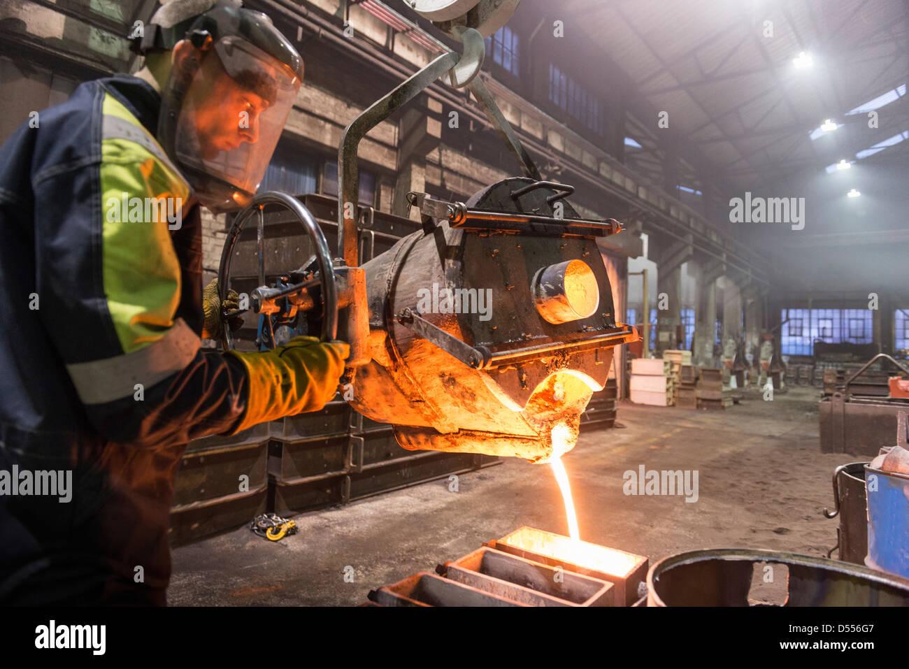Lavoratore di colata di metallo fuso in fonderia Immagini Stock