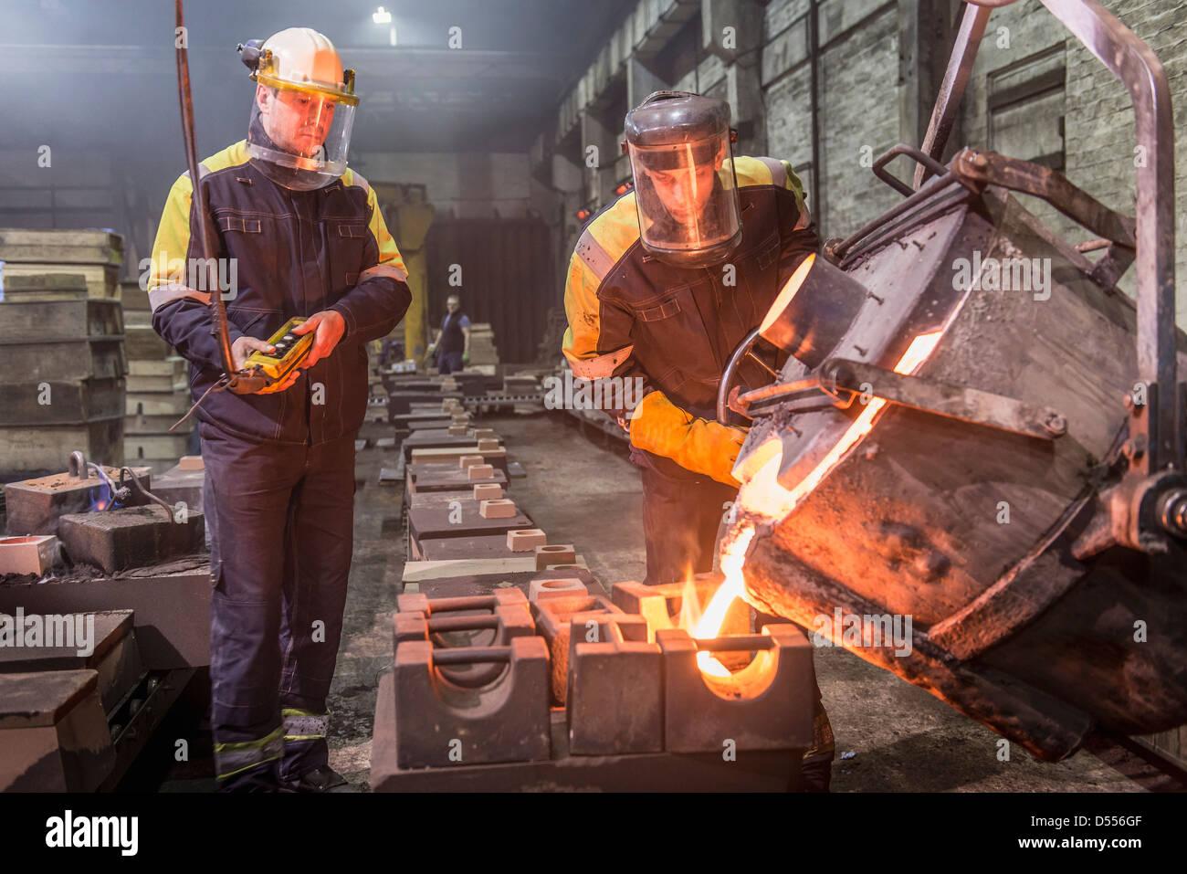 I lavoratori di colata di metallo fuso in fonderia Immagini Stock