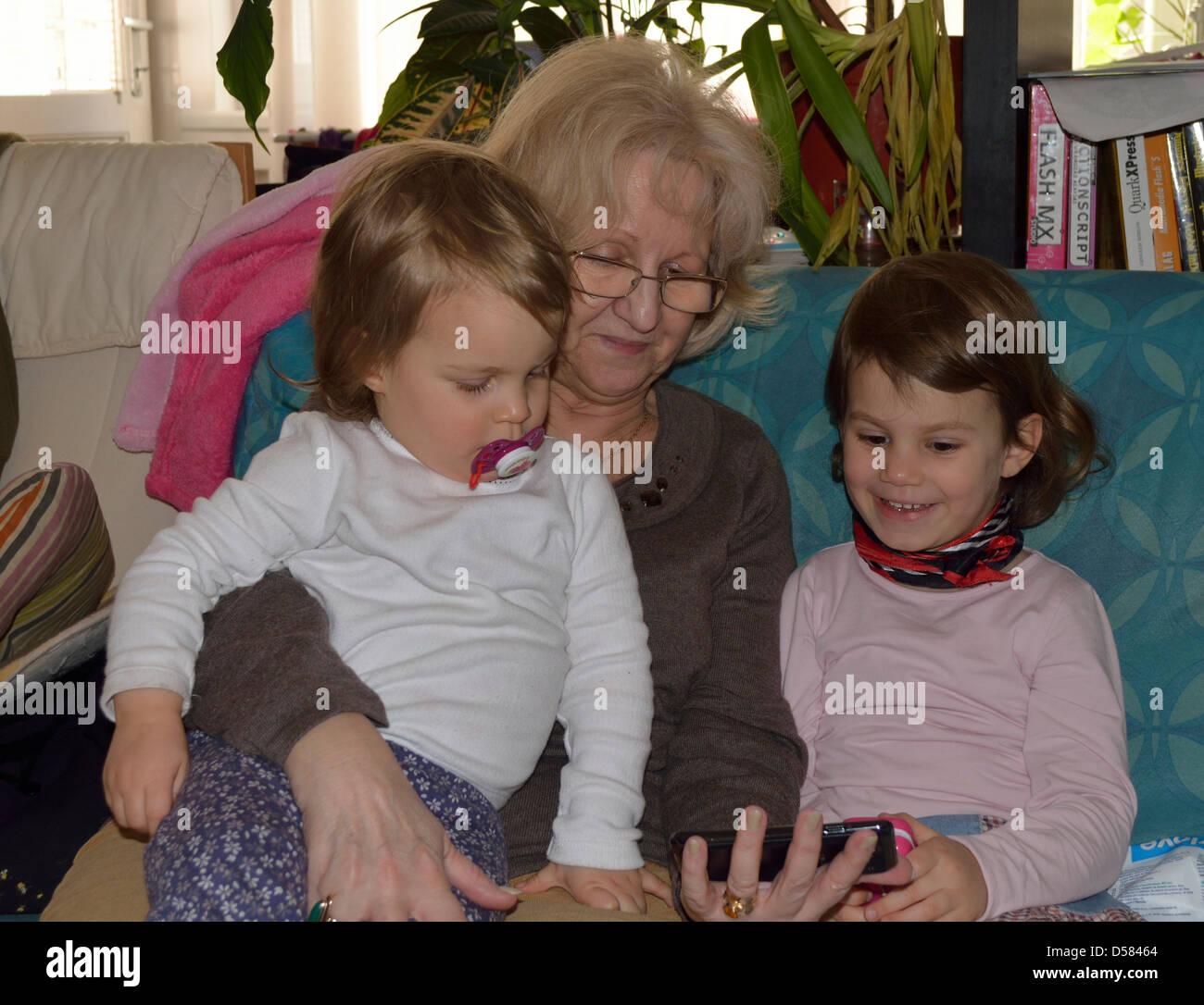 Bambini la visione di un cartone animato con la nonna Immagini Stock b41ae3ee67