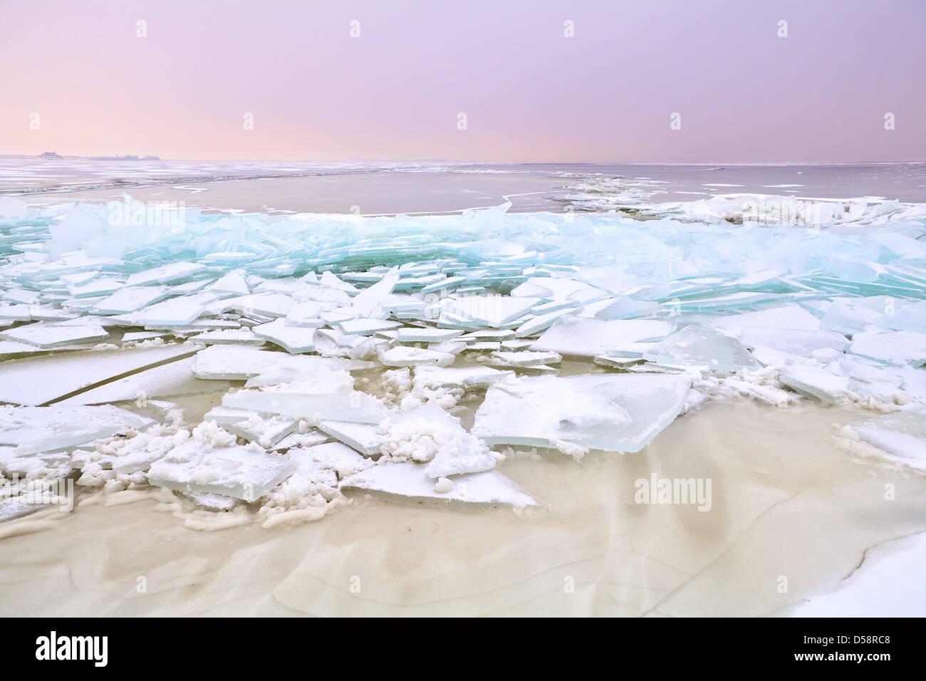 Ripiano sul ghiaccio congelato Ijmuiden al tramonto, Olanda Immagini Stock