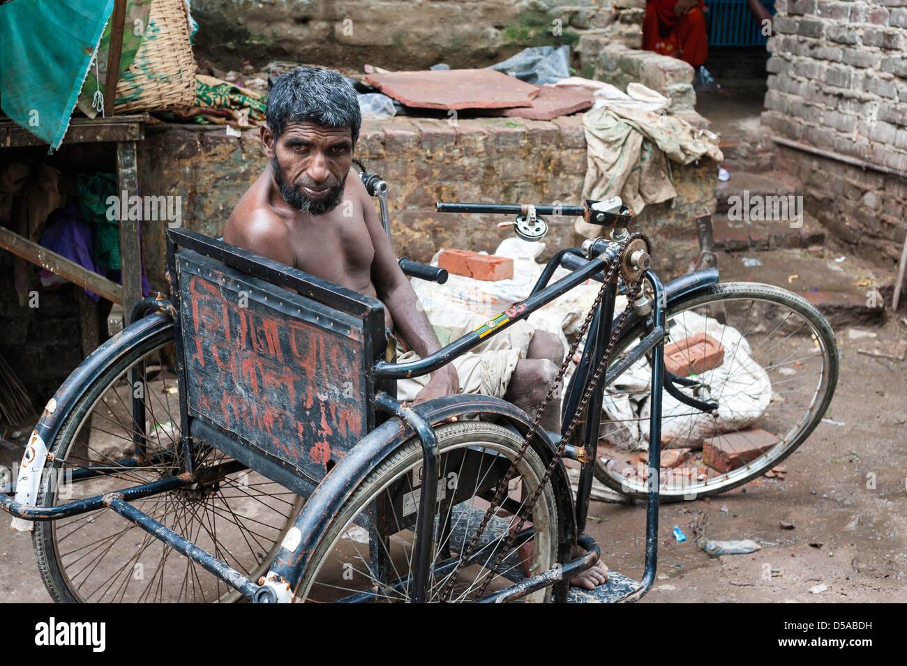 Uomo con disabilità in atto di triciclo accattonaggio in Nizamuddin, una parte vecchia di Delhi, India. Immagini Stock