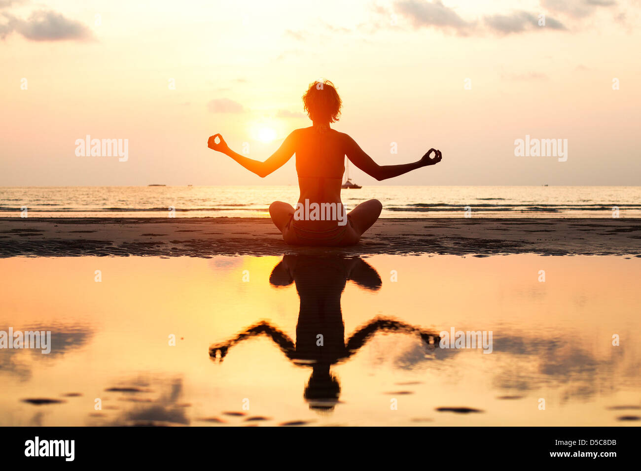 Yoga donna seduta in lotus pongono sulla spiaggia durante il tramonto, con riflessione in acqua, in colori luminosi. Immagini Stock