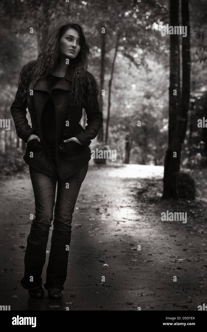 Donna che cammina verso il basso garden trail sul giorno di pioggia Immagini Stock