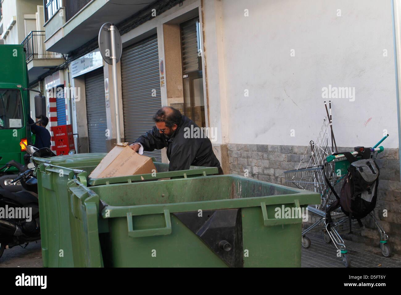 Un disoccupato uomo tira un carrello per trasportare la posta indesiderata trovati sui contenitori. Immagini Stock