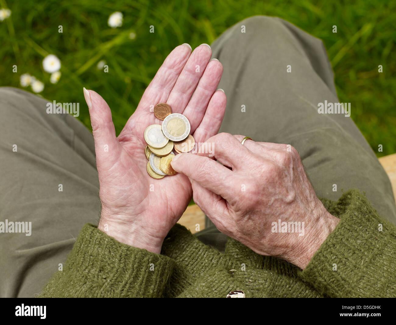 Le mani di un senior contando meno soldi, la povertà Immagini Stock