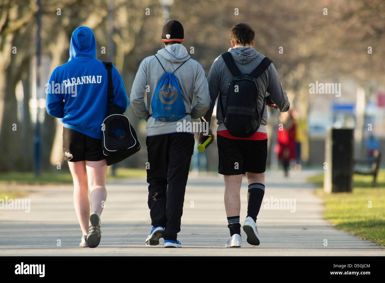 Vista posteriore di tre giovani uomini con il kit sacchetti sulle loro spalle a piedi o da una formazione sportiva Immagini Stock