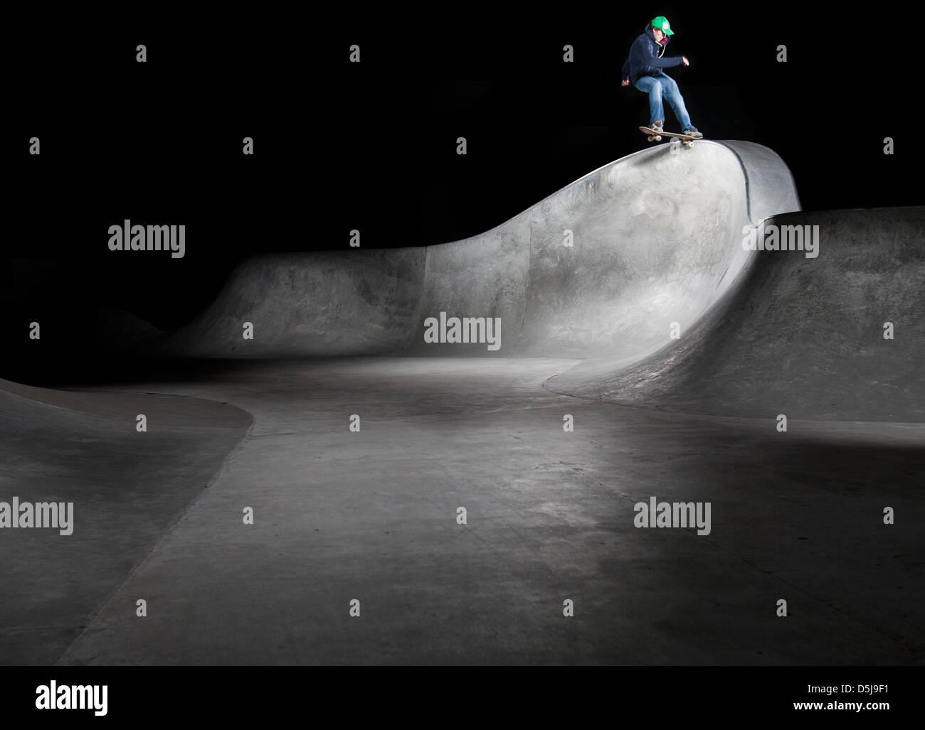 Un pattinatore giostre di notte in Saughtons outdoor skatepark in cemento Immagini Stock