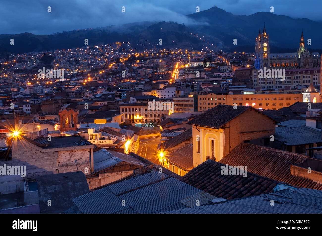 Quito, Ecuador città vecchia e la basilica di notte con le montagne sullo sfondo Immagini Stock