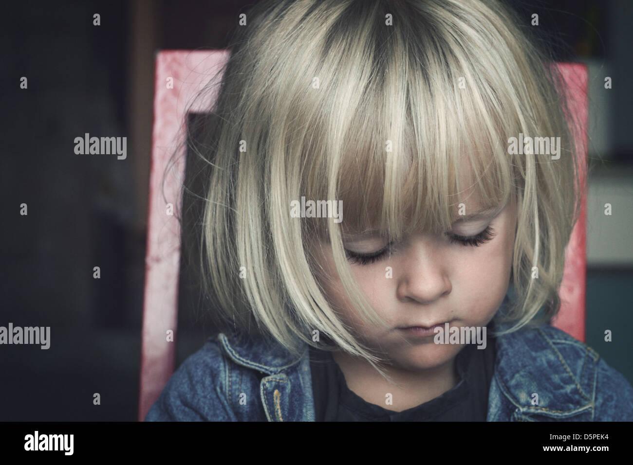 Triste piccolo bambino seduto su una sedia, guardando verso il basso Immagini Stock