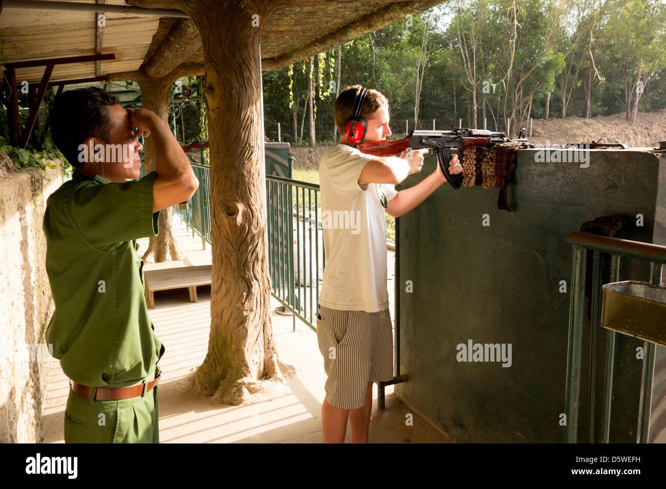Incendi turistica AK 47 Kalashnikov fucile automatico a tiro con la carabina al Cu Chi Viet Cong nel Tunnel di Cu Immagini Stock
