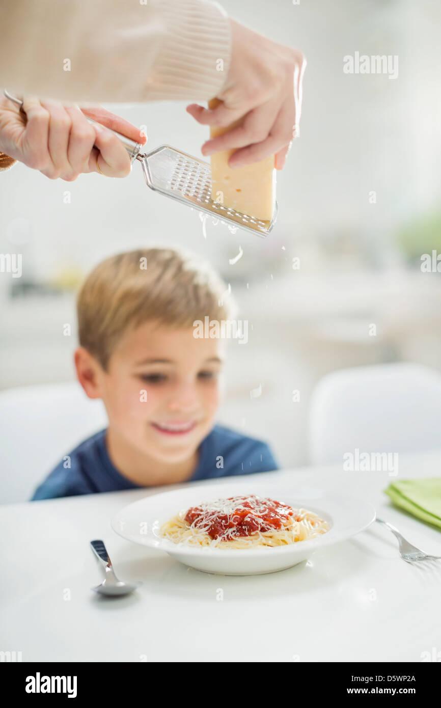 Madre grattugiare il formaggio oltre il figlio spaghetti Immagini Stock