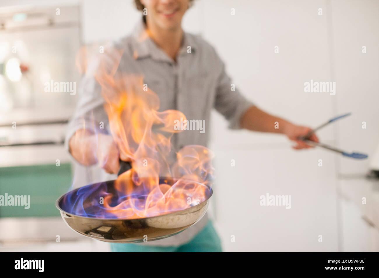 L'uomo la cottura con il fuoco in cucina Immagini Stock