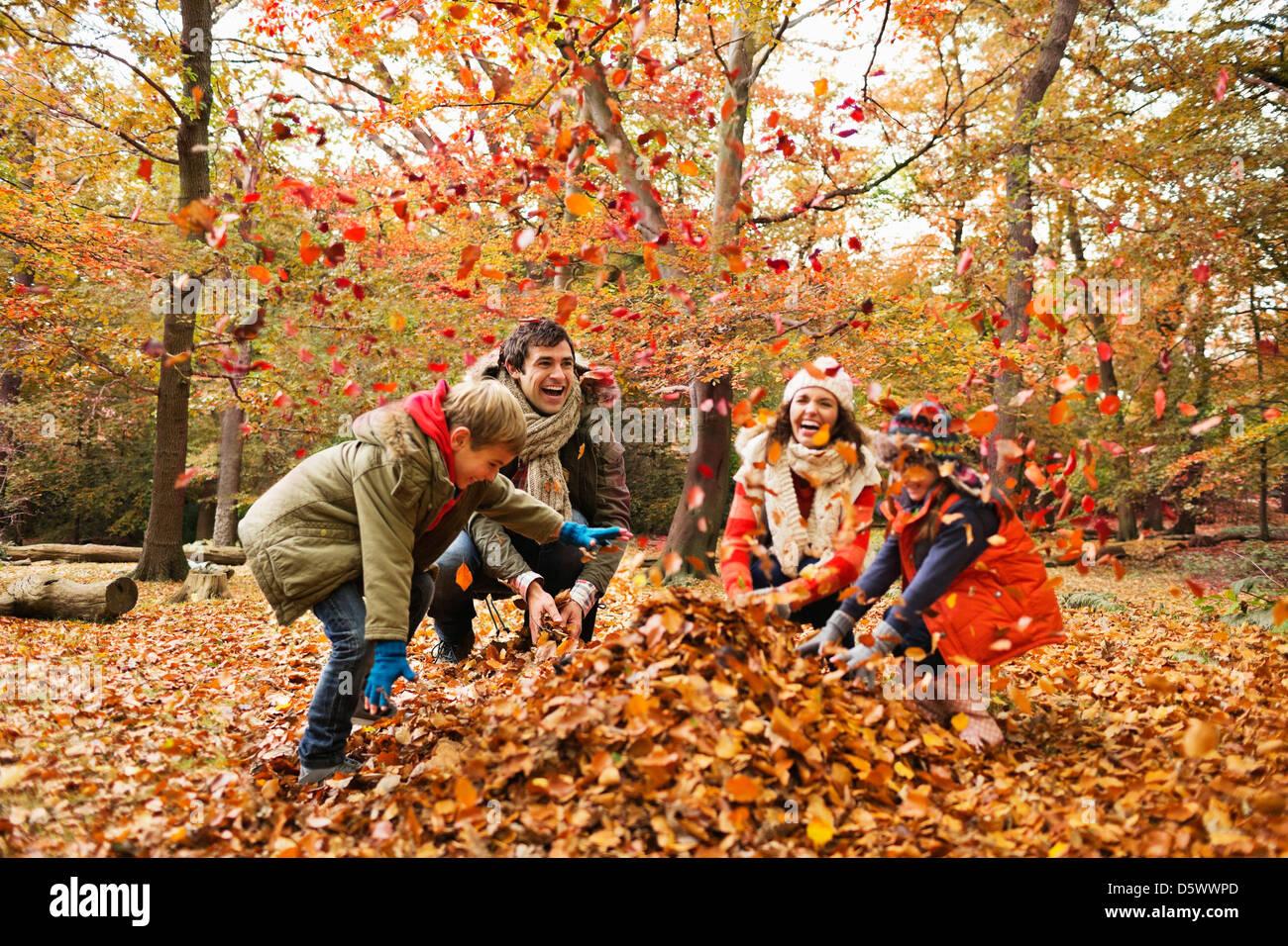Famiglia giocando in foglie di autunno Immagini Stock