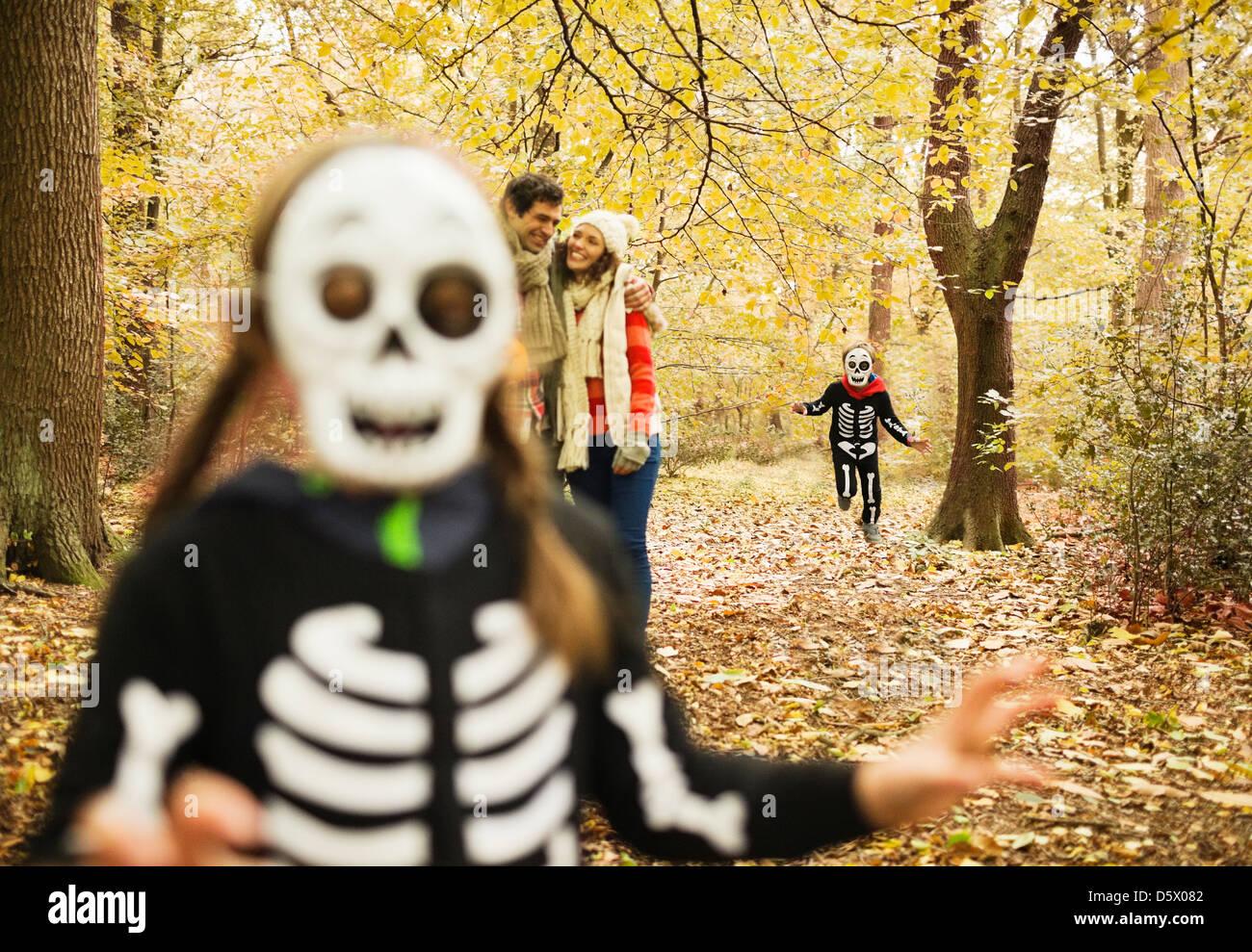 I bambini in costumi di scheletro a giocare nel parco Immagini Stock